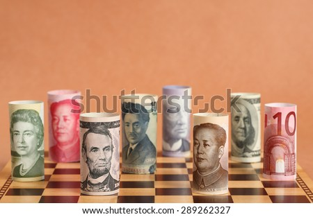 Currency War. Photo Shows Banknotes from Different Countries on a Chess Board. - stock photo