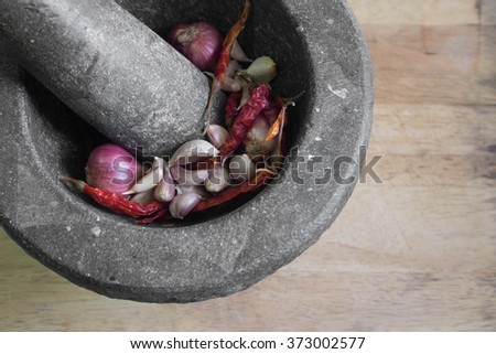 Curry Ingredients in rock mortar with pestle - stock photo