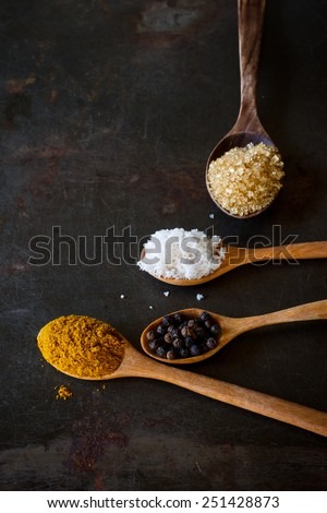 curry powder, salt, sugar and pepper heap in wood spoon soft focus , put on grunge metal background - stock photo