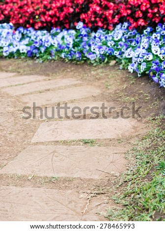 Curve block pathway with the colorful blooming garden. - stock photo