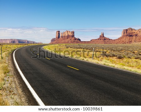 Curve in road in scenic desert road with mesa land formations and mountains. - stock photo