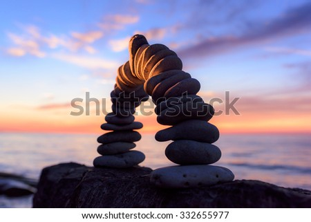 Curve of pebbles in the form of a arch on the coast in evening - stock photo
