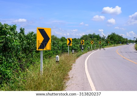 Curve road and right tuning sign with blue sky. - stock photo