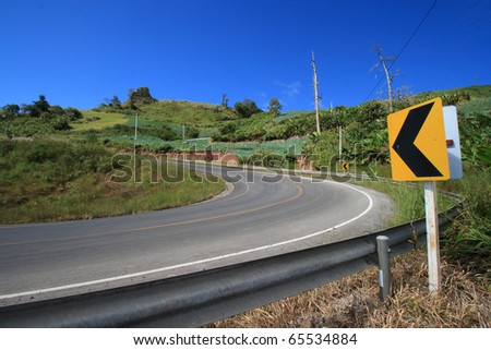 Curve road sign on up hill. - stock photo