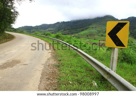 Curve road sign on up hill - stock photo