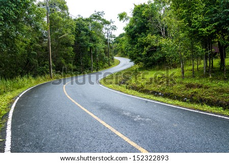 curve way of asphalt road through the green field - stock photo