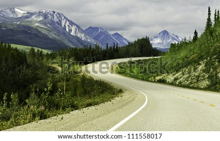 Curved asphalt road in high mountains of Alaska - stock photo