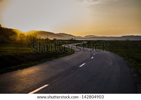Curved asphalt road running trough the meadows/On the curvy road again/ - stock photo