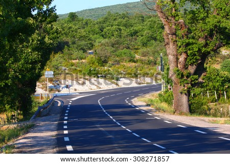Curved bend on country road in forest area - stock photo