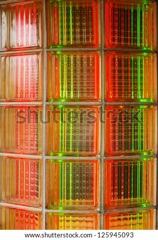 Curved glass brick wall lit from behind with red and green neon lights - stock photo