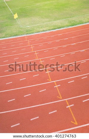 Curved part of running track with corner of football field - stock photo