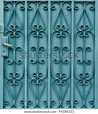 Curved pattern design on green metal door with handle - stock photo