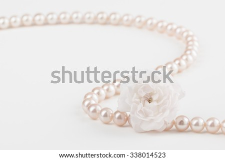 Curved pearl necklace with miniature rose, in muted pastel tones, with copy space. - stock photo