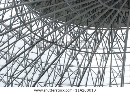 Curved reinforced steel roof joists in a conservatory with glass panes - stock photo