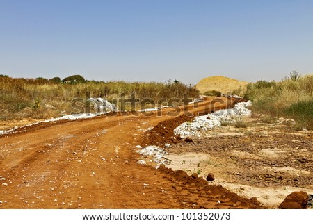 curved road going to a small hill on a sunny afternoon - stock photo