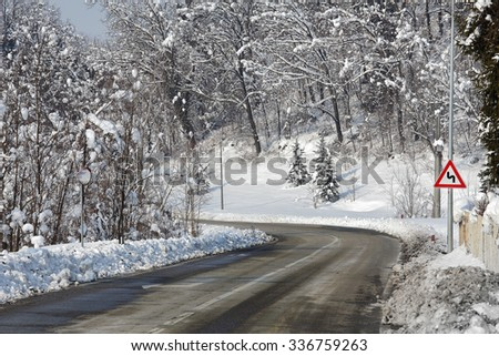 Curved road through among and hills covered with snow in winter in Piedmont, Northern Italy. - stock photo