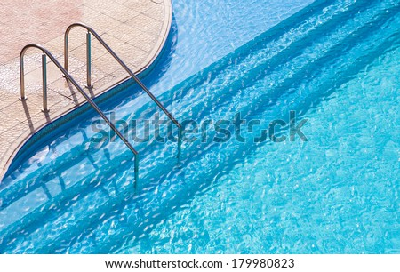 Curved side of a swimming pool with stairs. - stock photo