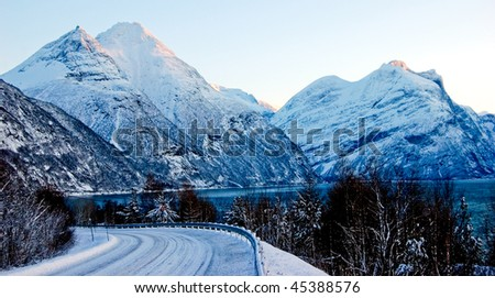 Curved snowy road in Norway, winter - stock photo