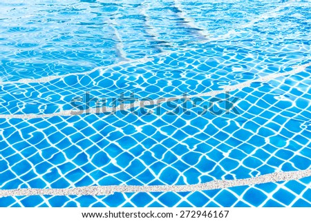 Curved steps at the resort swimming pool with blue water - stock photo