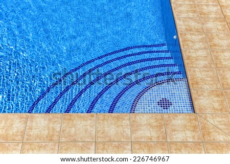 Curved steps into swimming pool, view from above through transparent water on blue mosaic tiles - stock photo