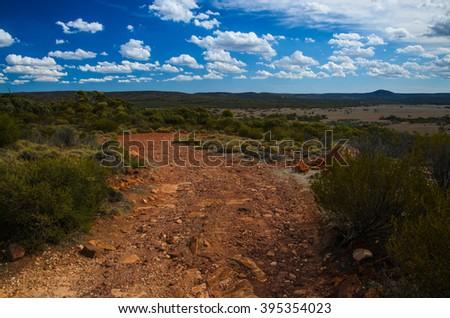 Curvy red soil dirt road Australian outback rural wilderness scene - stock photo