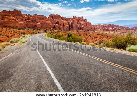 Curvy road in a dry and desert area with scenic view of orange mesas - stock photo
