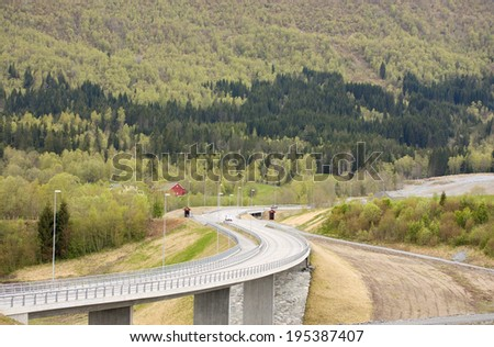 Curvy road with bridge in rural landscape - stock photo