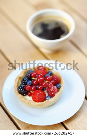 Custard fruit tart and cup of coffee in the outdoors cafe  - stock photo