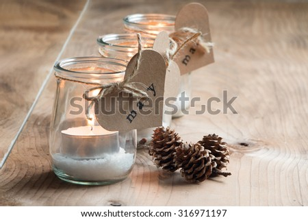 Custom and eco candle holders with jars and paper labels printed for a Christmas dinner - stock photo