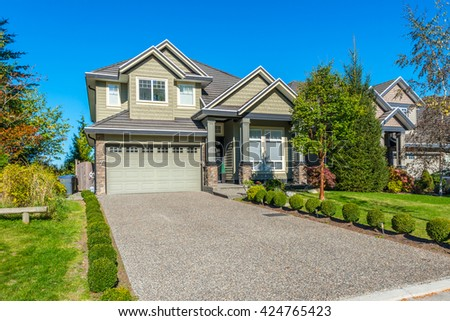 Custom built luxury house, townhouse with nicely trimmed and landscaped front yard, lawn and driveway to garage in a residential neighborhood. Vancouver Canada. - stock photo