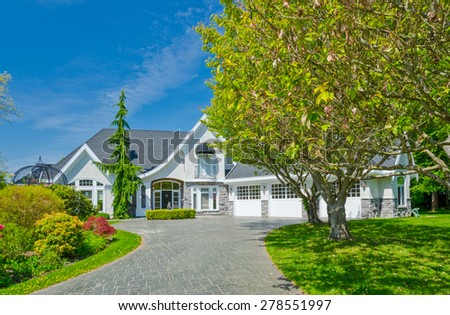 Custom built luxury house with nicely trimmed and decorated front yard, lawn and nicely paved driveway to garage in a residential neighborhood. Vancouver Canada. - stock photo