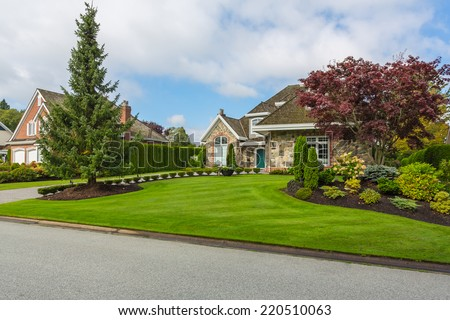 Custom built luxury house with nicely trimmed and designed front yard, lawn in a residential neighborhood. Vancouver Canada. - stock photo