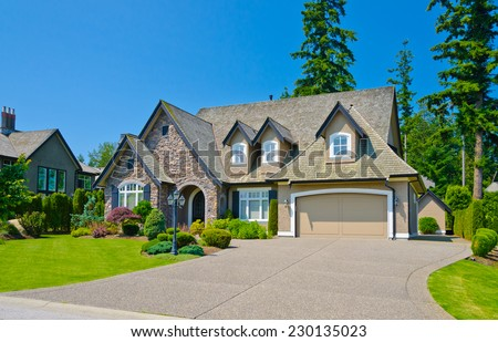 Custom built luxury house with nicely trimmed and landscaped front yard lawn and driveway to garage in a residential neighborhood. Vancouver Canada. - stock photo