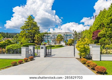 Custom built luxury house with nicely trimmed and landscaped front yard lawn and gated driveway in a residential neighborhood. - stock photo