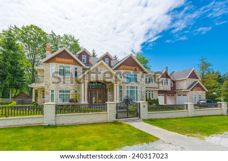 Custom built luxury house with nicely trimmed and landscaped front yard, lawn in a residential neighborhood. Vancouver, Canada. - stock photo