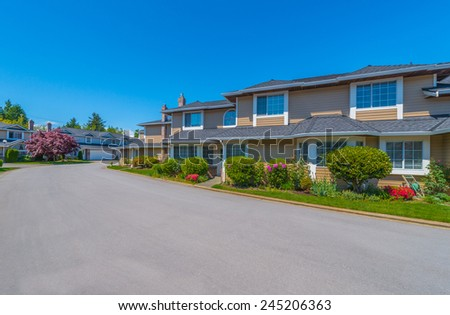 Custom built luxury house with nicely trimmed and landscaped front yard lawn in a residential neighborhood. Vancouver Canada. - stock photo