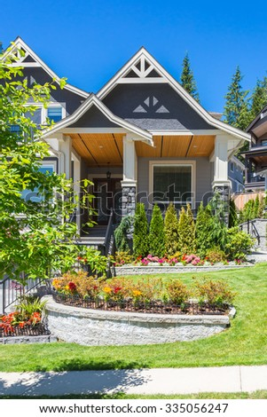 Custom built luxury house with nicely trimmed and landscaped front yard lawn in a residential neighbourhood. Front entrance. - stock photo