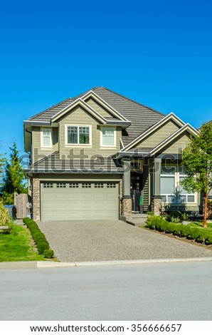 Custom built luxury house with nicely trimmed front yard, lawn and driveway in a residential neighborhood. Vancouver Canada. - stock photo