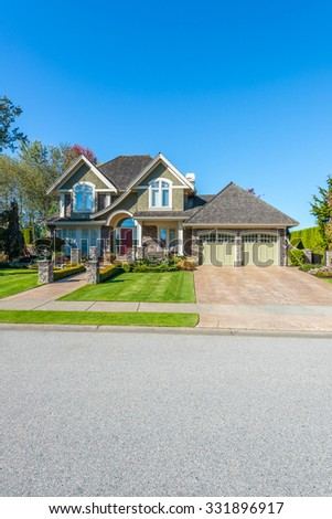 Custom built luxury house with nicely trimmed front yard, lawn and long doorway and driveway in a residential neighborhood. Vancouver Canada. Vertical. - stock photo
