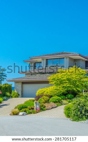 Custom built luxury house with nicely trimmed front yard, lawn and paved driveway to garage in a residential neighborhood. Vancouver Canada. Vertical. - stock photo