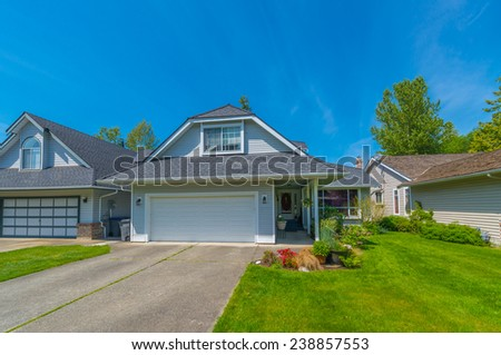 Custom built luxury house with nicely trimmed front yard, lawn and wide driveway to the double doors garage in a residential neighborhood. Vancouver Canada. - stock photo