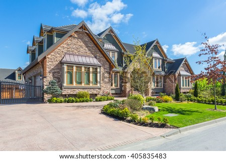 Custom built luxury house with nicely trimmed front yard, lawn in a residential neighborhood. - stock photo
