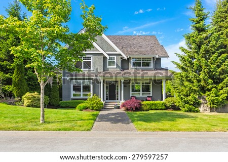 Custom built luxury house with nicely trimmed front yard, lawn in a residential neighborhood in North America on a sunny day. - stock photo