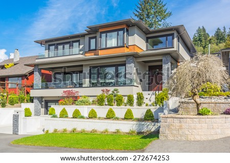 Custom built luxury modern house with nicely trimmed and landscaped front yard lawn and driveway to garage in a residential neighborhood. Vancouver Canada.  - stock photo