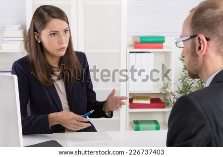 Customer and female financial agent in a discussion at desk. - stock photo