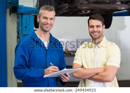 Customer and mechanic smiling at camera at the repair garage - stock photo