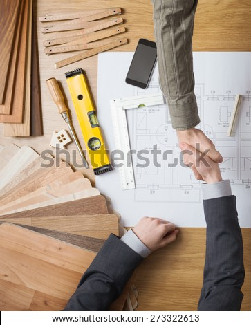 Customer businessman and construction engineer working together on a building project, they are shaking hands, desktop with draft and tools on background, top view - stock photo