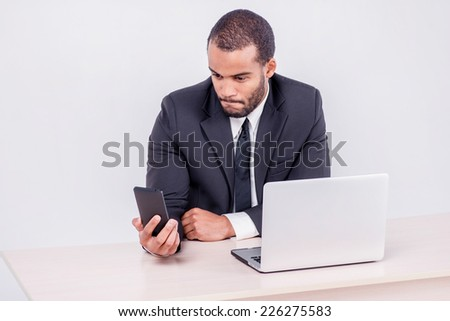Customer call. Smiling African businessman sitting at a desk and looking at mobile phone while businessman sitting at the table and working on a laptop isolated on a gray background - stock photo