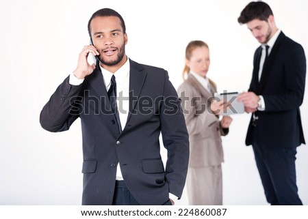 Customer call. Successful and smiling African businessman talking on cell phone while his colleagues are working on a tablet in the background on a gray background - stock photo