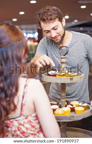 Customer choosing cupcakes in the shop - stock photo